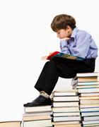 Photo of young boy reading a manual while sitting on top of book stack Stock Photos