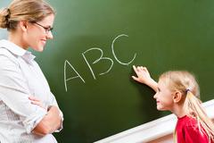 Image of smart girl pointing at letter on blackboard and looking at her teacher Stock Photos