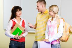 Photo of smart teenager standing and explaining something to serious girl in col Stock Photos