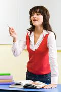 portrait of confident teacher standing at her desk with open textbook on it - stock photo