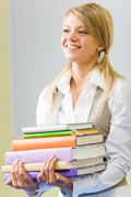 Portrait of cheerful student with pile of books in hands Stock Photos