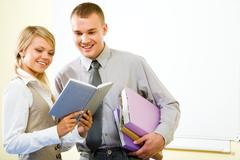 portrait of two successful students looking into notebook together with smiles - stock photo