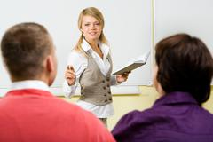 Image of clever teacher with book in hand explaining something to the students a Stock Photos