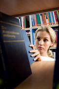 Image of young girl searching for necessary book on bookshelf in library Stock Photos