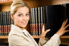 Portrait of business lady touching books that stand on shelf and looking at came Stock Photos