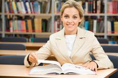 portrait of happy student sitting in library before textbook and looking at came - stock photo