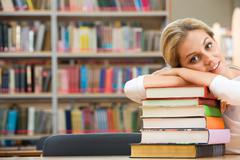 Portrait of tired student lying on the stack of books Stock Photos
