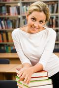 Portrait of young woman keeping her arms on the top of book stack in the library Stock Photos