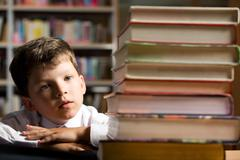 face of diligent schoolboy looking at stack of books in the library - stock photo