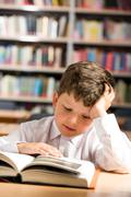 Vertical image of interested schoolkid reading book in the library Stock Photos