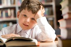 Photo of young boy sitting at the table in the library Stock Photos