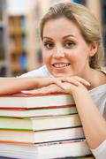 Portrait of pretty student putting her chin on hand over pile of books Stock Photos