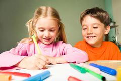 Image of classmates sitting next to each other during drawing lesson Stock Photos