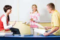 Image of two teenagers sitting on desk with smiling girl standing near by and ha Stock Photos