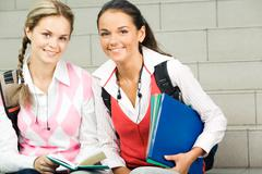 portrait of two students sitting next to each other and looking at camera - stock photo