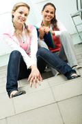 photo of two casually dressed girls sitting on stairs of college and looking at - stock photo