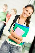 Portrait of cute girl holding textbook in hands on background of reading student Stock Photos