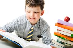 Portrait of schoolboy reading story with heap of books and apple near by Stock Photos