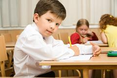 Image of smart schoolboy sitting at desk and drawing while looking at camera dur Stock Photos