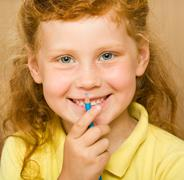 Face of red-headed girl holding blue pencil by her mouth looking at camera with Stock Photos
