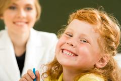 Close-up of happy girl laughing while looking at camera on background of smart t Stock Photos