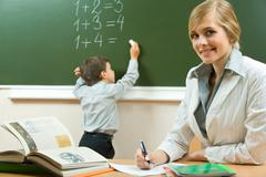 portrait of pretty teacher sitting at the table on the background of schoolboy - stock photo
