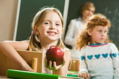 Portrait of happy pretty girl holding a red apple in the classroom Stock Photos