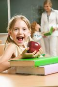 portrait of happy schoolgirl and apple in her hands sitting at the table with bo - stock photo