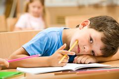 close-up of tired pupil with yellow crayon putting his head on arm and looking a - stock photo
