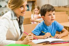 portrait of young teacher sitting by one of pupils while both looking at somethi - stock photo