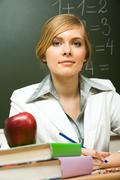 portrait of confident teacher sitting at her desk with stack of books and apple - stock photo