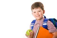 Portrait of cute schoolboy holding green apple and book looking at camera over w Stock Photos