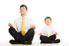 Photo of father and son sitting in pose of lotus with their eyes closed and medi Stock Photos