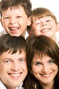 photo of smiling father, mother and two siblings looking at camera - stock photo