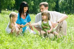 Portrait of happy family sitting on the lawn in the forest Stock Photos