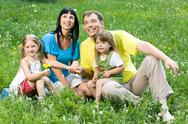 Stock Photo of portrait of little girl giving flower to her mother with father and sister near
