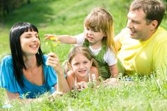 Portrait of family having rest on grass while little girl reaching for flower in Stock Photos