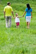 portrait of family walking down green meadow at leisure in summer - stock photo