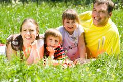 Portrait of family lying on grass in the park in summer and enjoying themselves Stock Photos