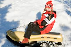Portrait of smiling girl sitting on the sledge in the forest Stock Photos