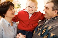 Portrait of happy grandparents and their grandson smiling at camera Stock Photos