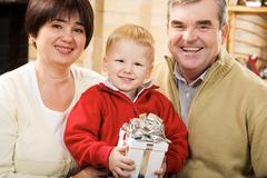 Stock Photo of portrait of happy grandparents and their grandson smiling at camera
