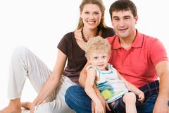 Photo of mother, father and son looking at camera on a white background Stock Photos