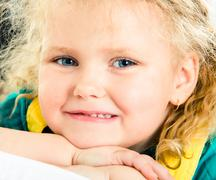 Face of pretty little girl looking at camera with smile with her chin on hands Stock Photos