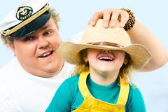 Photo of man putting hat on his daughter's head while she laughing Stock Photos