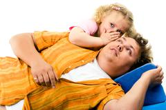portrait of father and his daughter lying on the bad - stock photo