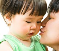 Close-up of mother kissing her small daughter lovingly over white background Stock Photos