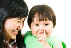 image of happy mother looking at her cute little daughter with smile - stock photo