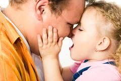 Profile of loving father with daughter touching his cheek and cuddling up to him Stock Photos