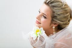 close-up of charming bride holding flower by her chin and looking straight - stock photo